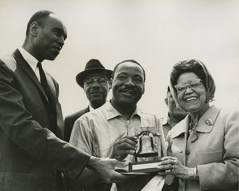 Martin Luther King, Jr., being presented replica Liberty Bell by Sadie Tanner Mossell Alexander and Terry Crisholm at civil rights march from Selma, AL, to Montgomery, AL